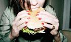 Young woman biting into burger