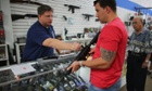 Jonathan Schwartz (L), a salesman at the National Armory gun store, helps Reese Magnant as he looks to buy a National Armory AR-15 Battle Entry Assault Rifle in Pompano Beach, Florida. President Barack Obama today in Washington, DC announced a broad range of gun initiatives that his administration thinks will  help curb gun violence.