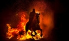 A man rides a horse through a bonfire in San Bartolome de Pinares, Spain in honor of Saint Anthony, the patron saint of animals.
