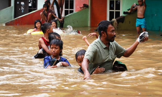 A father escorts his son as they evacuate a flooded area in Jakarta, Indonesia. Heavy monsoon rains caused severe flooding. and thousands of people have been forced to leave their homes
