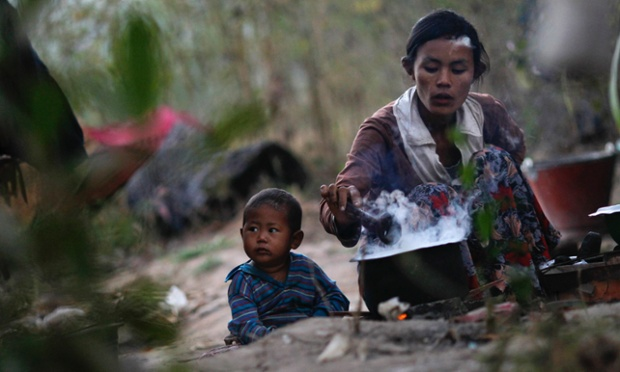 Waiting for supper. A boy sits near his mother as she cooks rice in a field outside Rangoon, Burma.