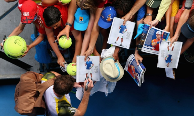 Andy Murray signs an autograph after winning his second round match against Joao Sousa of Portugal at the Australian Open in Melbourne.