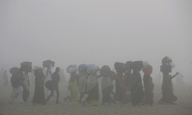 People walk through thick fog on their way to bathe in the Bay of Bengal at Puri, in the eastern Indian state of Orissa.