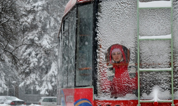 A commuter looks through a snow-covered window of a tram in the Belarusian capital, Minsk, where temperatures have dropped to -6C