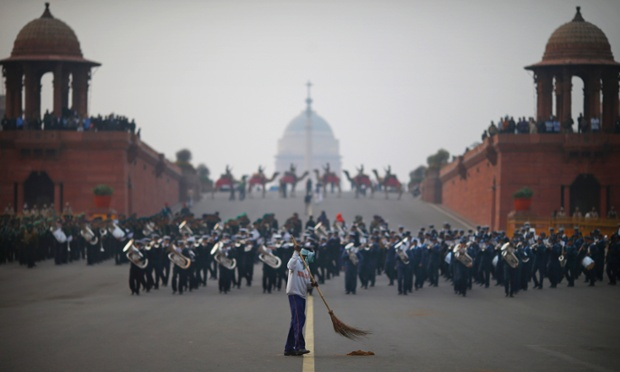 A worker sweeps a road as military bands practise for the upcoming Beating Retreat ceremony near the presidential palace in New Delhi, India