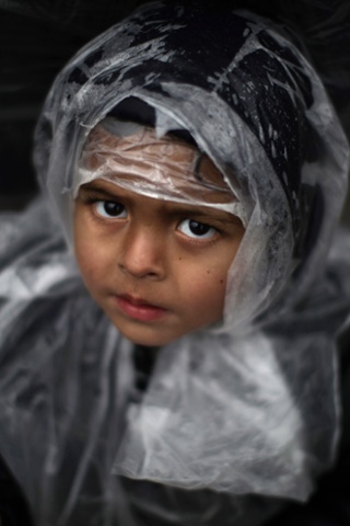 A Pakistani boy wrapped up in a plastic sheet to shield the rain during an anti-government rally in Islamabad, Pakistan.