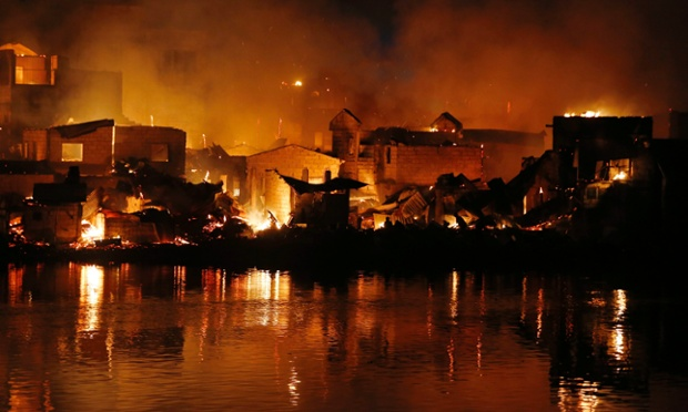 Burning houses are seen from across a river during a fire in a residential area in Cainta town, Rizal province, east of Manila, Philippines. More than 100 houses were gutted by the blaze.