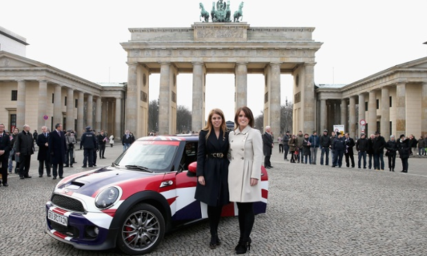 Princess Beatrice and Princess Eugenie pose next to their Mini in front of Brandenburg Gate as they promote the UK abroad. They will visit Hanover tomorrow as part of the two-day trip funded by their father, the Duke of York