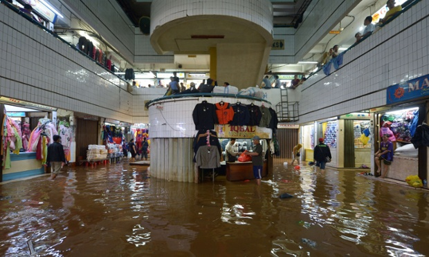 Market vendors try to go about businesses as usual despite floodwaters in Jakarta