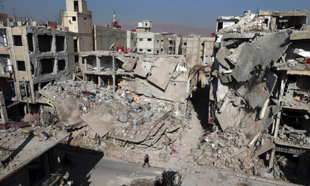 A man walks past buildings destroyed by Syrian air force air strikes in the Duma neighbourhood of Damascus