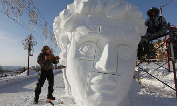 Members of a Russian team work on a snow sculpture based on a creation by Michelangelo during the 1st International festival