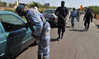 Malian police officers control cars at a checkpoint near Bamako Senou airport