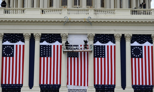 Two workers adjust US flags on the US Capitol as preparations continue for the second inauguration of US President Barack Obama in Washington, DC.