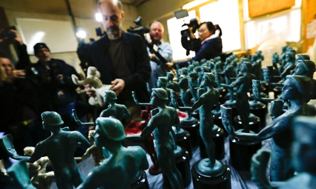 Nominated actor David Marciano (C) places a shell mold back on a table next to rows of finished patina coated and mounted statuettes of