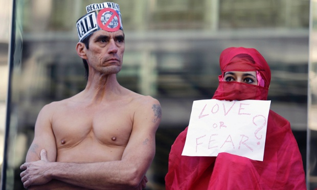 Natalie Mandeau (R) of France, holds up a sign during a demonstration against a nudity ban outside a federal building in San Francisco. Activists are asking a federal judge to block a city ordinance banning public nudity. The ban is scheduled to go into effect Feb. 1.