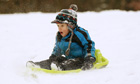 Adam Burgess, four, enjoys a ride on his sled during heavy snowfall in Buckinghamshire