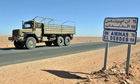 An Algerian military truck drives past a road sign for the city of In Amenas