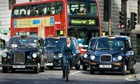 Woman cycles in London traffic