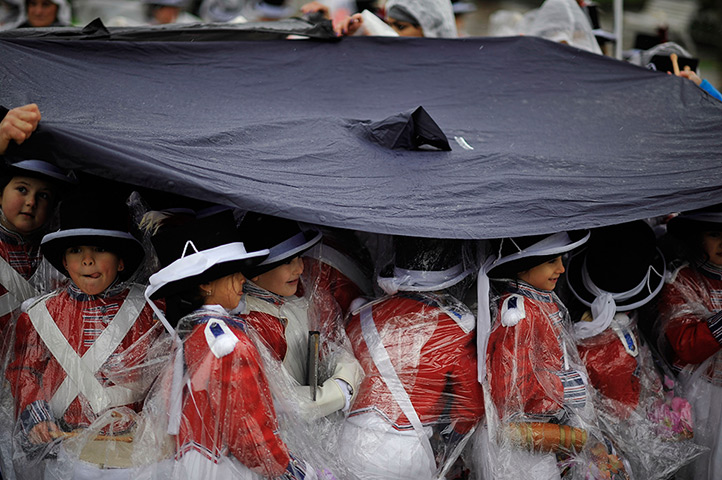 24 hours: San Sebastian, Spain: Tamborilleros wear protection against rain