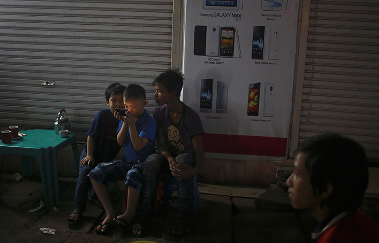 24 hours: Rangoon, Burma: Children use a mobile phone
