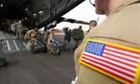 A U.S. soldier looks on as French soldiers exit a U.S. Air Force C-17 transport plane in Bamako, Mali. The United States has started transporting French soldiers and equipment to Mali as part of its logistical aid to French forces fighting Islamist militants in the north of the country.