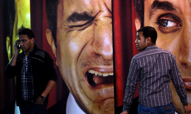 Egyptian men walk past posters of Egyptian satirist Bassem Youssef ...