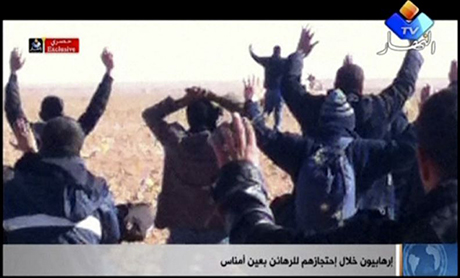Hostages kneel in the sand with their hands in the air. Photo: AP