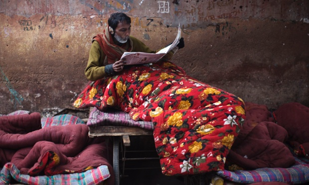 A photograph documenting daily life in Delhi pictures a homeless man tucked up with his newspaper on a cold winter morning. Heavy fog and freezing temperatures in Northern India have killed scores of homeless in the state of Uttar Pradesh.