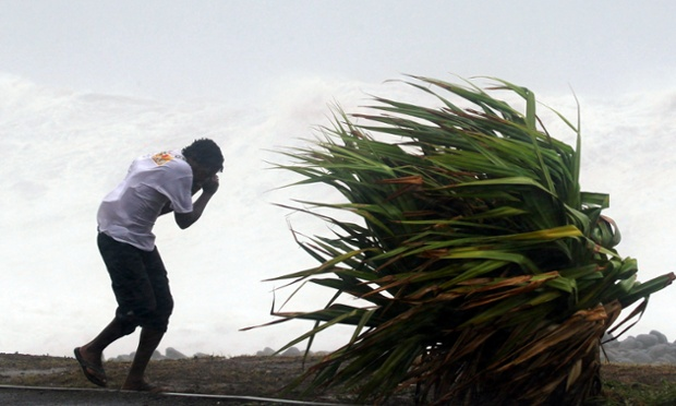 A man struggles against strong wind in the western part of the island of La Reunion as cyclone Dumile approaches. Authorities have declared a red alert urging people not to leave their homes.