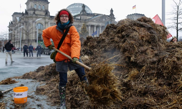 What a heap of muck...quite literally! An activist from the anti-globalisation organisation Attac poses with a  a pile of manure in front of the Reichstag parliament building, in Berlin, Germany. Attac unloaded the manure in a protest over social fairness.