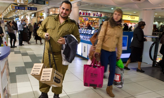 An Israeli soldier holds two gas mask kits he picked up as he travels through the central bus station in Jerusalem. Media reports that thousands of Israelis are renewing their gas masks after reports of an Israeli air force strike on an arms convoy inside Syria.