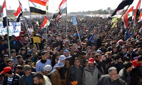 Sunni Muslims wave national flags yesterday during an anti-government demonstration in Samarra, northern Iraq.