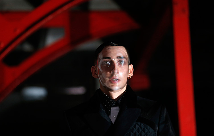 Male model wearing polka dotted collar shirt, a jacket and a plastic, transparent full face mask