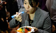 A Japanese reporter tries out the HAPIfork at CES