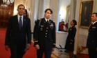 US President Barack Obama walks with William Swenson, prior to awarding him the medal of honor.