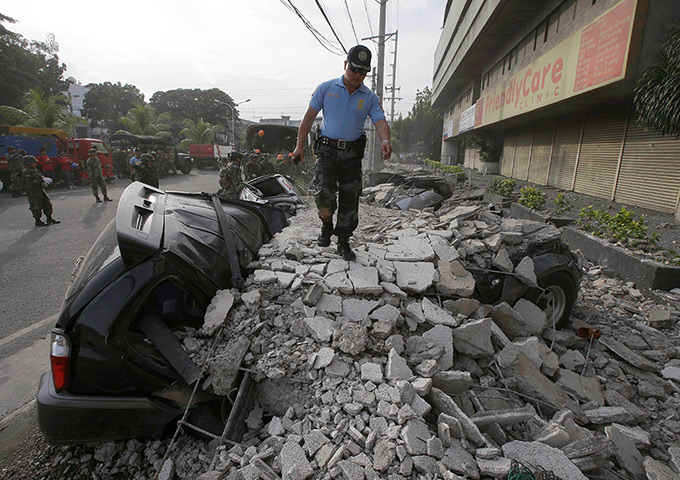 Philippines earthquake: A police officer walks on a topped wall in Cebu city