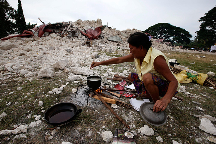 Philippines earthquake: A woman cooks in front of the remains of the church of Our Lady Of Light, i