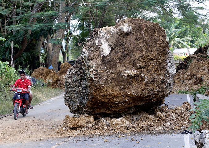 Philippines earthquake: People ride past a giant boulder in the road in Cortez town