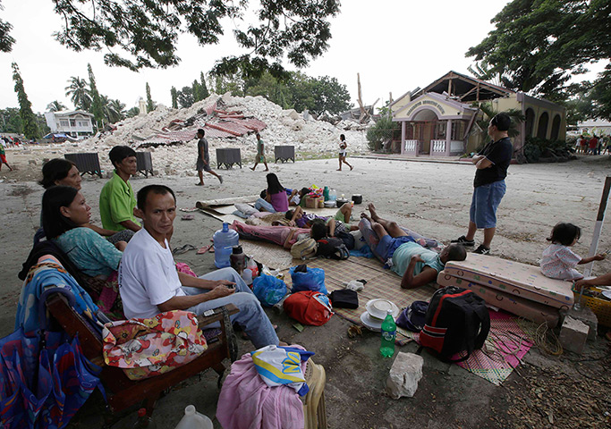 Philippines earthquake: Residents camp outside to avoid aftershocks near the ruins of the collapsed