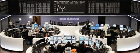 Traders are pictured at their desks in front of the DAX board at the Frankfurt stock exchange October 16, 2013.