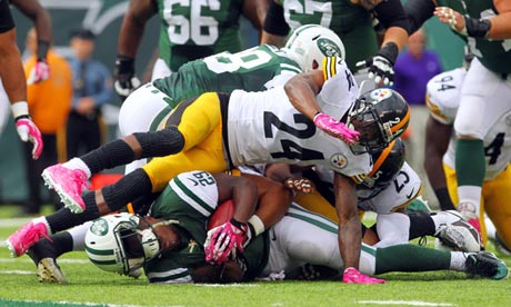 Jets running back Bilal Powell is tackled by Steelers cornerback Ike Taylor