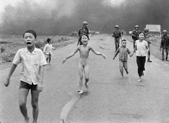 Severely burned in an aerial napalm attack, children run screaming for help down Route 1 near Trang Bang, followed by soldiers of the South Vietnamese army's 25th Division, on 8 June 8 1972. A South Vietnamese plane seeking Viet Cong hiding places accidentally dropped its flaming napalm on civilians and government troops instead. Nine-year-old Kim Phuc (centre) had ripped off her burning clothes while fleeing. The other children (from left) are her brothers Phan Thanh Tam, who lost an eye, and Phan Thanh Phouc, and her cousins Ho Van Bon and Ho Thi Ting. This photo won the 1973 Pulitzer prize for spot news photography ~ Photograph: Nick Ut/AP