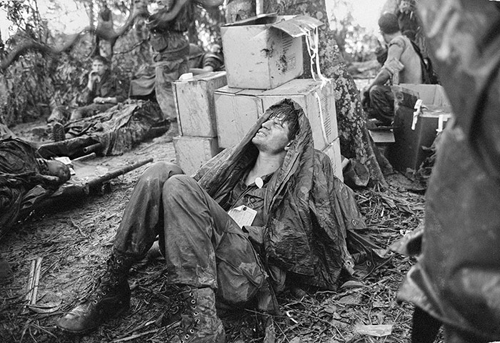 A US paratrooper wounded in the battle for Hamburger Hill grimaces in pain as he awaits medical evacuation at base camp near the Laotian border on 19 May 19 1969 ~ Photograph: Hugh Van Es/AP