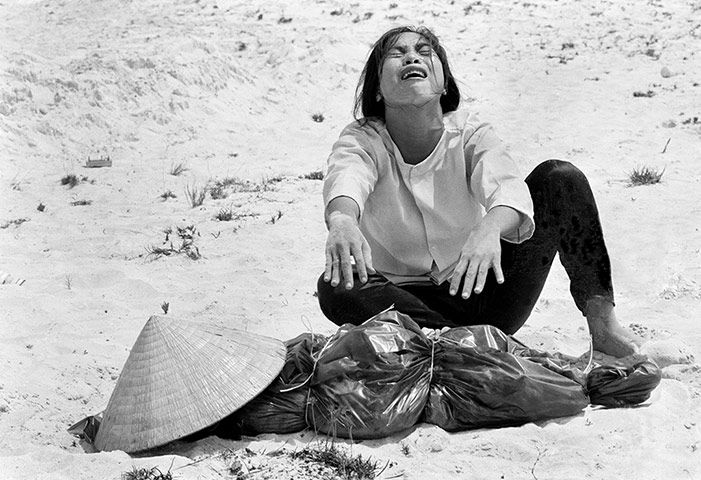 A woman mourns over the body of her husband after identifying him by his teeth, and covering his head with her conical hat. The man's body was found with 47 others in a mass grave near Hue on 11 April 1969. The victims were believed killed during the insurgent occupation of Hue as part of the Tet offensive ~ Photograph: Horst Faas/AP
