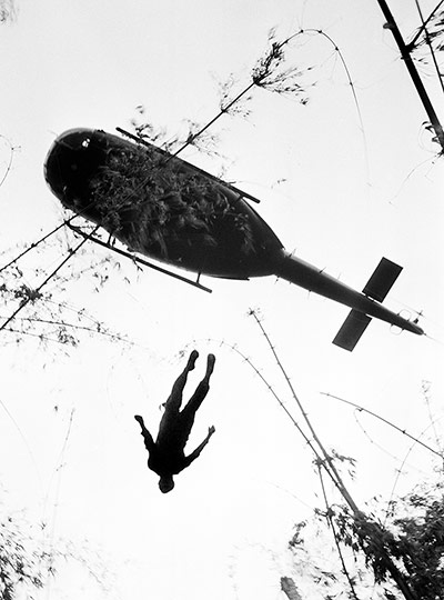 The body of a US paratrooper killed in action in the jungle near the Cambodian border is lifted up to an evacuation helicopter in War Zone C on 14 May 1966. The zone, encompassing the city of Tay Ninh and the surrounding area north of Saigon, was the site of the Viet Cong's headquarters in South Vietnam ~ Photograph: Henri Huet/AP