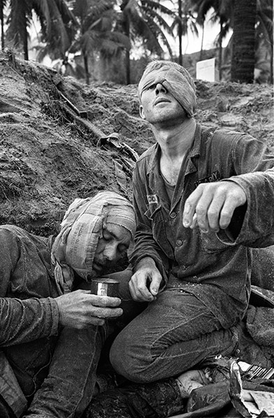 Medic Thomas Cole looks up with his one unbandaged eye as he continues to treat wounded Staff Sergeant Harrison Pell during a firefight on 30 January 1966. The men belonged to the 1st Cavalry Division, which was engaged in a battle at An Thi, in the Central Highlands, against combined Viet Cong and North Vietnamese forces. This photo appeared on the cover of Life magazine on 11 February 1966, and photographer Henri Huet's coverage of An Thi received the Robert Capa Gold Medal from the Overseas Press Club ~ Photograph: Henri Huet/AP
