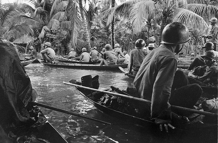 Caught in a sudden monsoon rain, part of a company of about 130 South Vietnamese soldiers moves downriver in sampans during a dawn attack on a Viet Cong camp on 10 January 1966. Several guerrillas were reported killed or wounded in the action thirteen miles northeast of Can Tho, in the flooded Mekong delta ~ Photograph: Horst Faas/AP