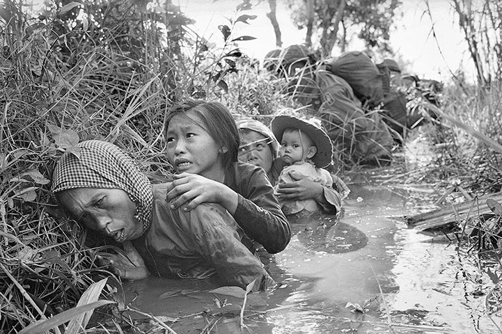 Women and children crouch in a muddy canal as they take cover from intense Viet Cong fire on 1 January 1966. Paratroopers of the 173rd Airborne Brigade (background) escorted the civilians through a series of firefights during the US assault on a Viet Cong stronghold at Bao Trai, about twenty miles west of Saigon ~ Photograph: Horst Faas/AP
