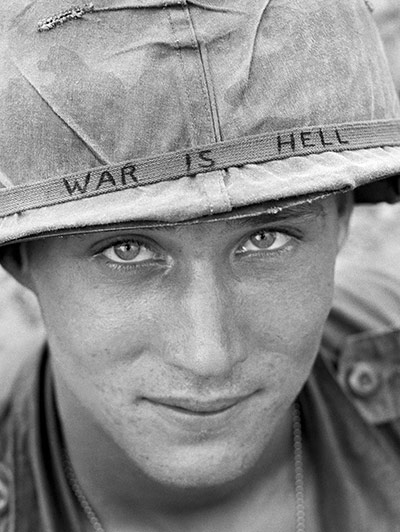 An unidentified American soldier wears a hand-lettered slogan on his helmet in June 1965. The soldier was serving with the 173rd Airborne Brigade on defense duty at the Phuoc Vinh airfield ~ Photograph: Horst Faas/AP
