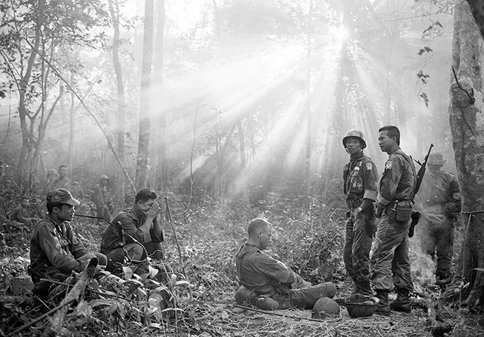 Sunlight breaks through dense foliage around the town of Binh Gia as South Vietnamese troops, joined by US advisers, rest after a cold, damp, and tense night of waiting in an ambush position for a Viet Cong attack that did not come in January 1965. One hour later, the troops would move out for another long, hot day hunting the guerrillas in the jungles forty miles southeast of Saigon ~ Photograph: Horst Faas/AP